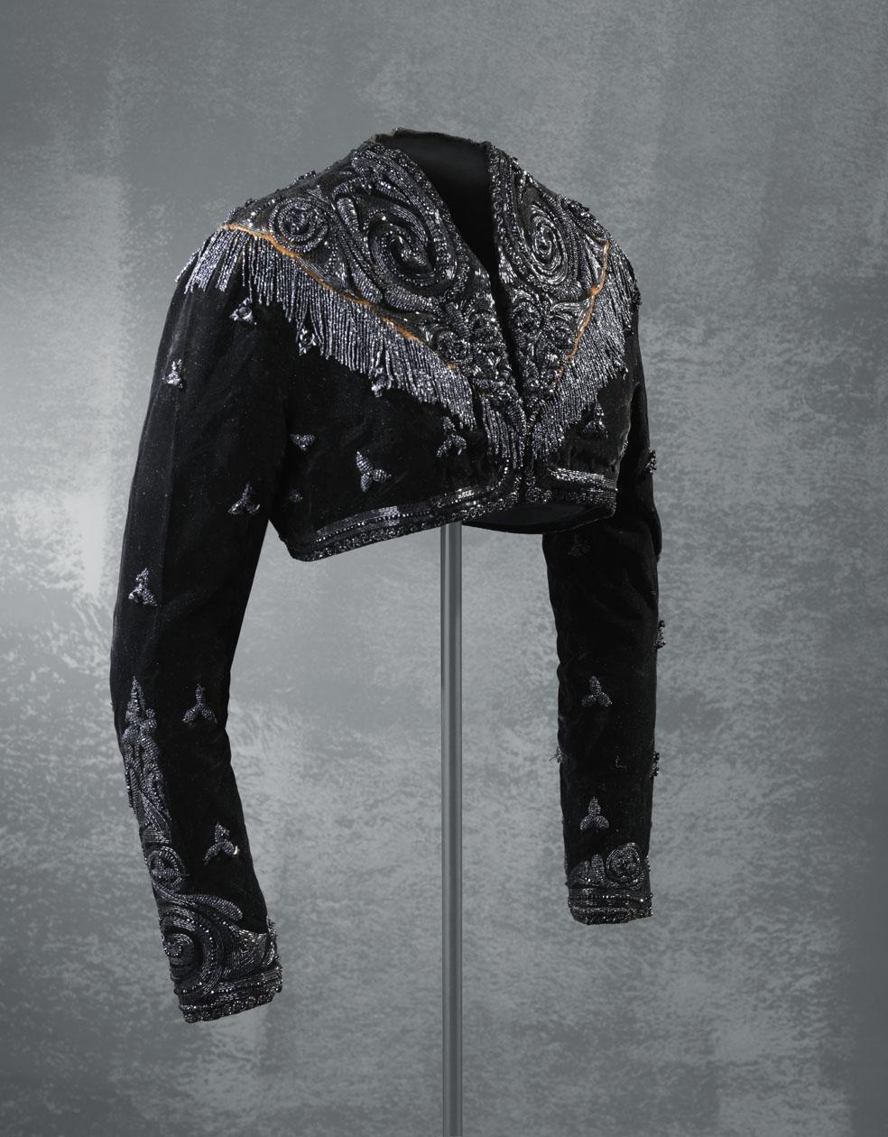 Chaqueta en terciopelo liso de color negro, guarnecida con una aplicación de mostacillas de azabache que dibujan motivos vegetales y flecos