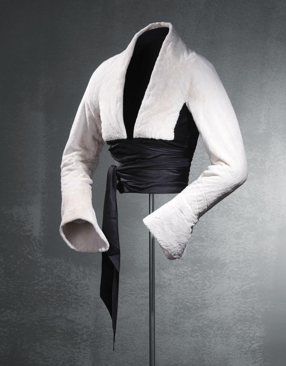 Chaqueta corta en piel de armiño de color blanco y satén negro en las cintas