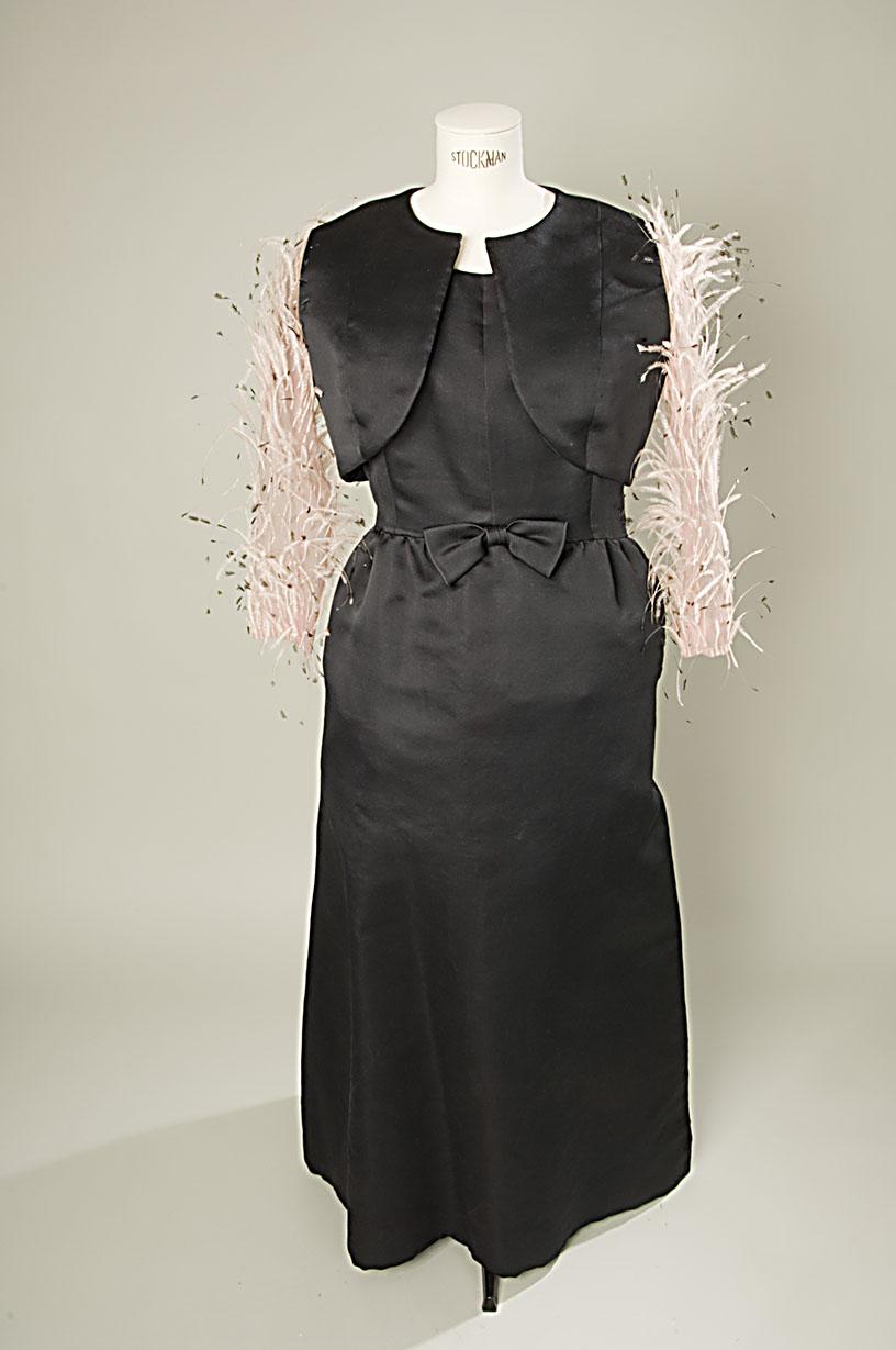 Bolero de raso negro el cuerpo con mangas en organza de seda rosa y aplicación de plumas de avestruz