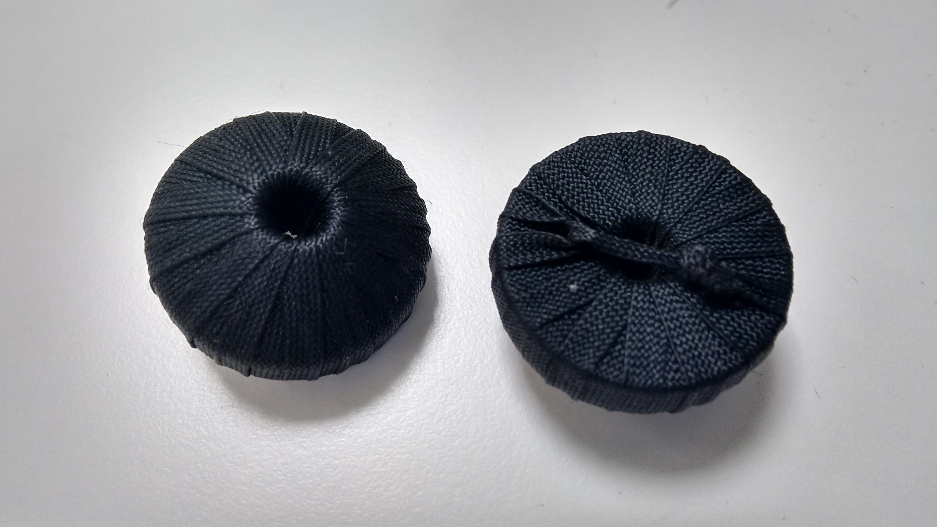 Botones redondos forrados de cinta negra.