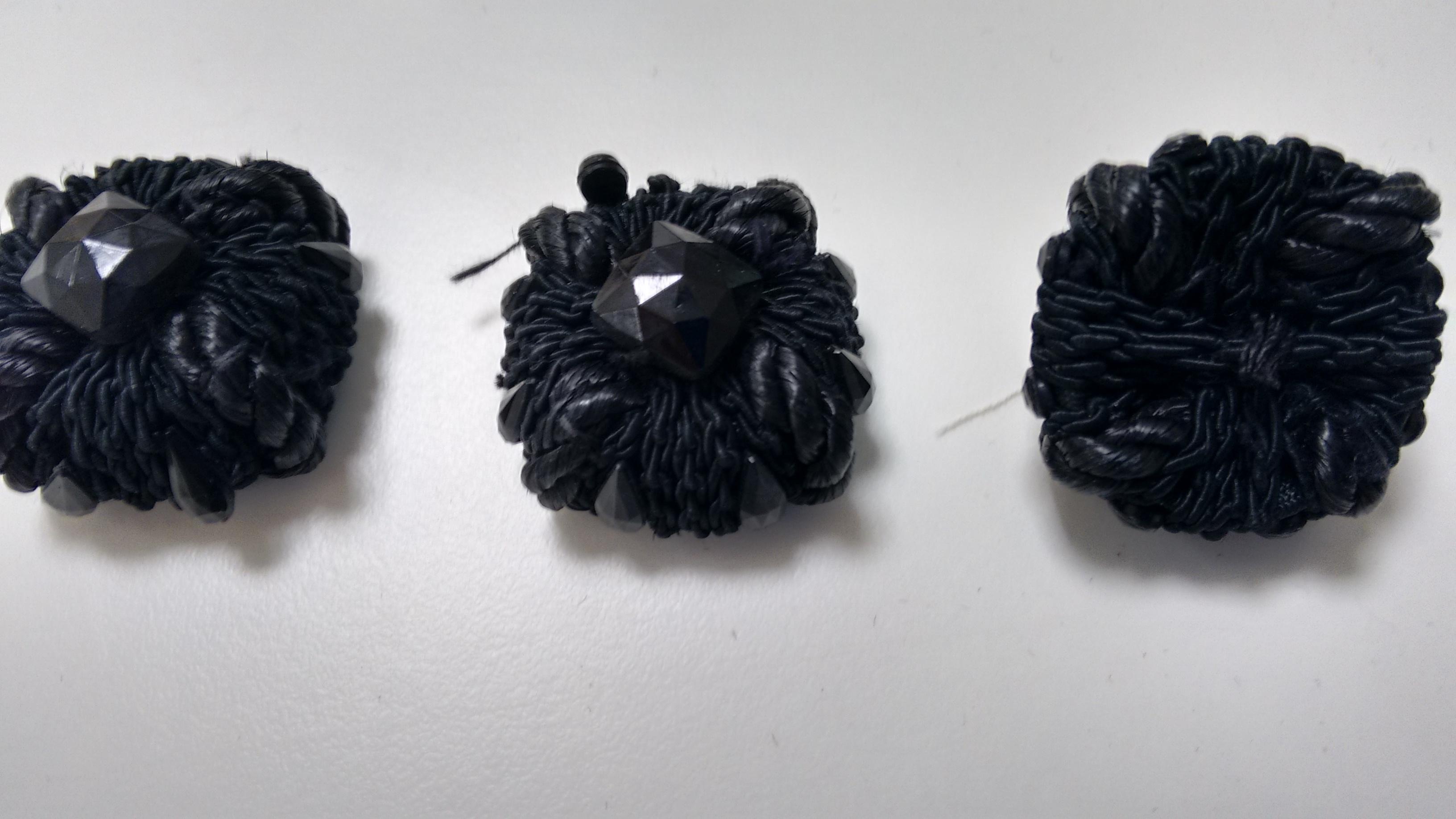 Botones  de cordoncillo negro y piedras facetadas negras.