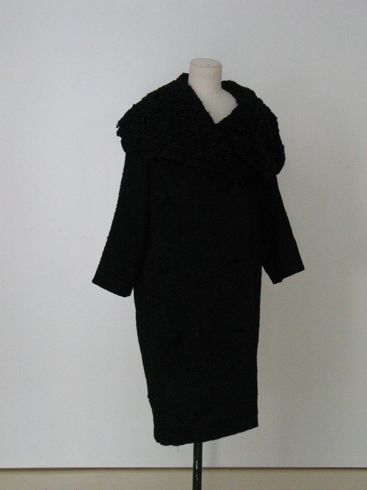 Abrigo corto en lana negra con botonadira doble y gran cuello de astracán.