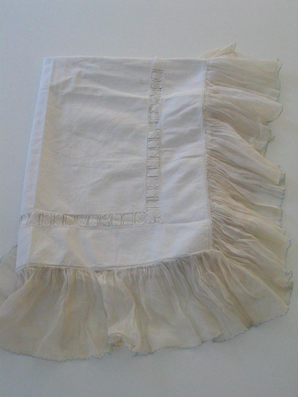 Cubrecuna de pique blanco, adornado con cinta de tira bordada y volantes de gasa.