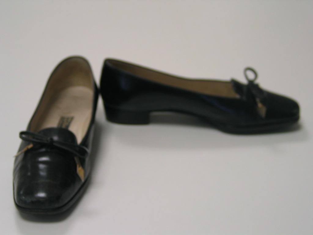 Zapatos de cuero negro con cordones de cuero rematados con adorno dorado