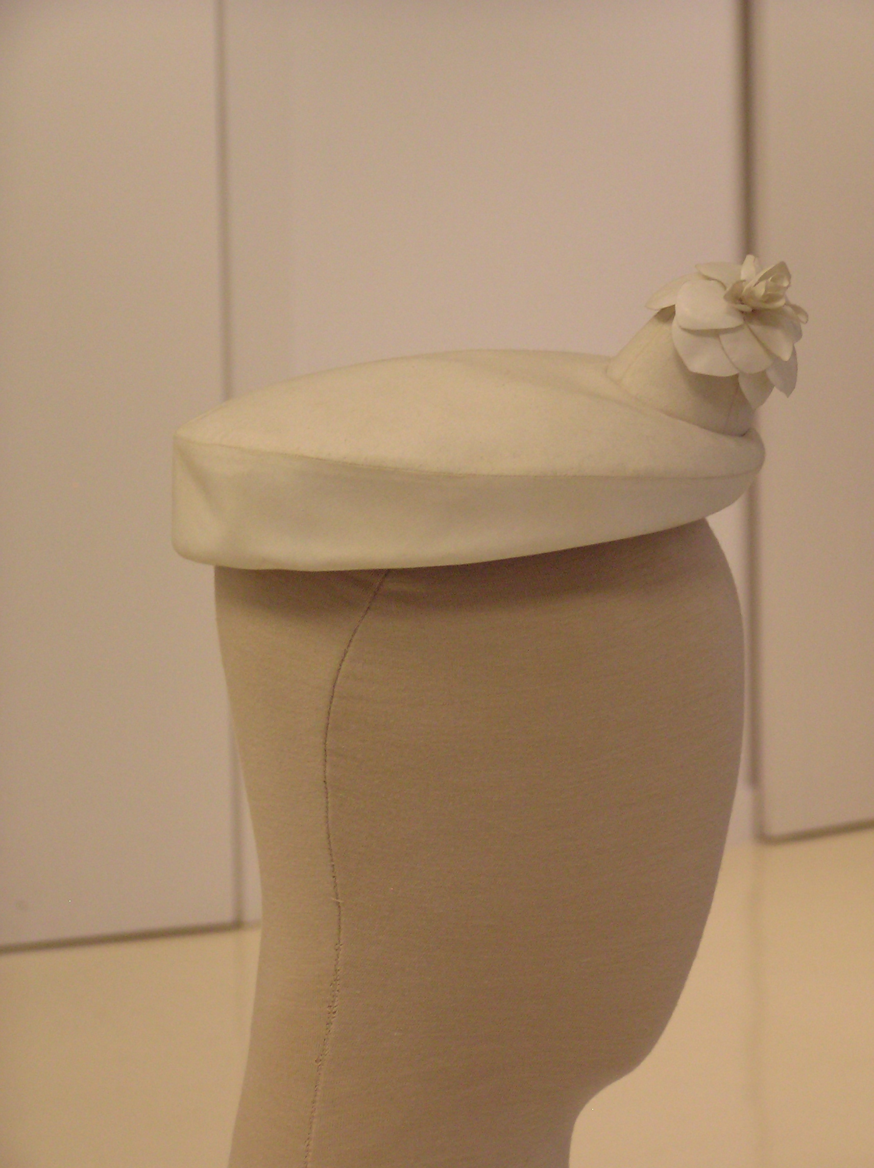 Tocado- Pillbox en algodón blanco con adorno cónico adornado con flor.