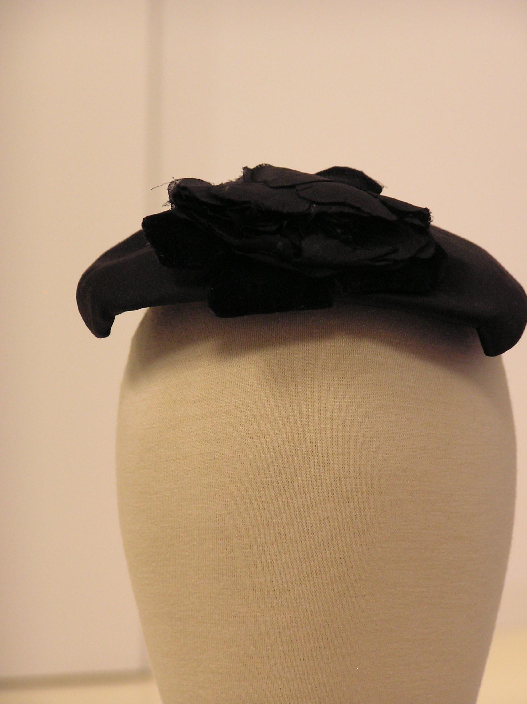 Tocado semiovalado en raso negro, con adorno floral