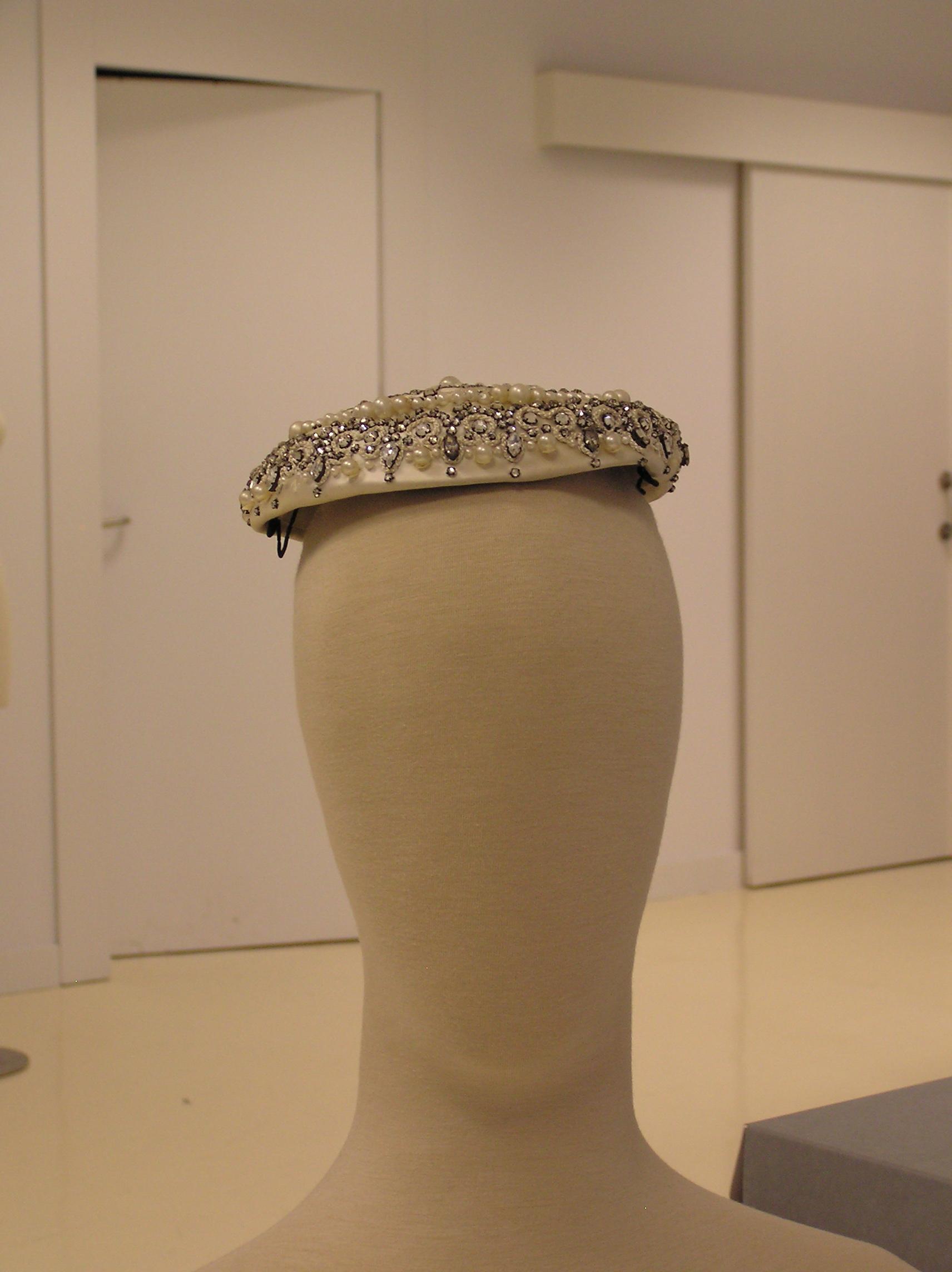 Tocado en raso marfil bordado con perlas y cristales facetados.