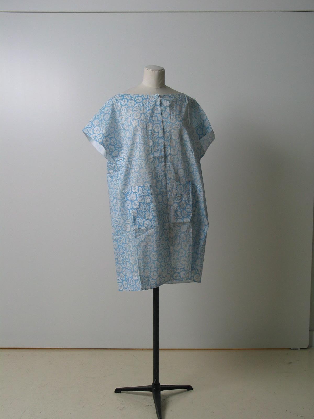 Bata en algodón blanco con estampación azul , realizando motivos florales por reserva.