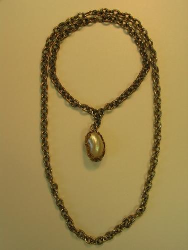 Dos perlas japonDos perlas ovaladas unidas por metal dorado colgando de una cadena de metal doradoesas ovaladas unidas por metal dorado colgando de una cadena de metal dorado