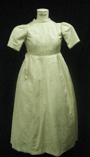 Vestido largo de niña realizado en tejido de seda en canalé blanco e hilo metálico