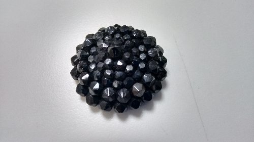 Botón  redondo adornado con piedras facetadas negras.