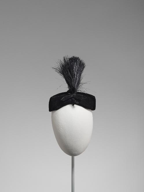 Pillbox en terciopelo negro con penacho de plumas negras y lazo de terciopelo negro en el frente.