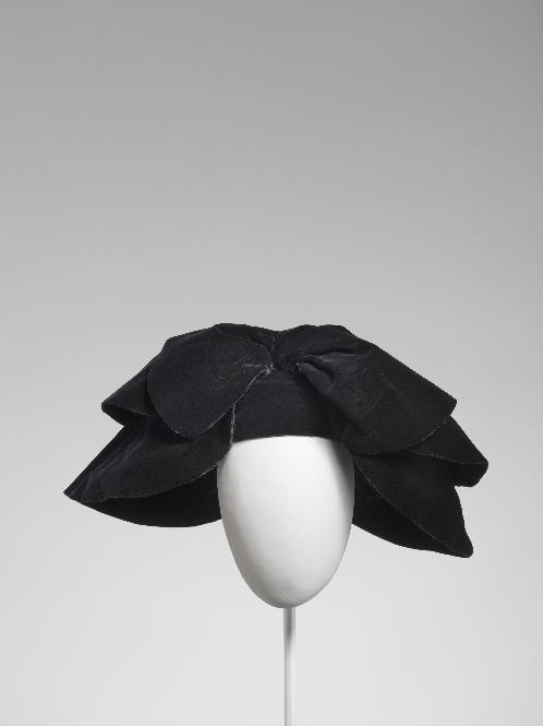 Tocado en terciopelo negro con petalos plegados.